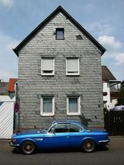 Blauer Sportwagen vor einem Altbau mit Schieferfassade