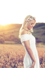 Beautiful young woman standing in wheat and enjoy