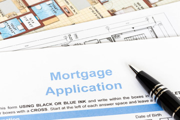 House mortgage application with pen and construction plan
