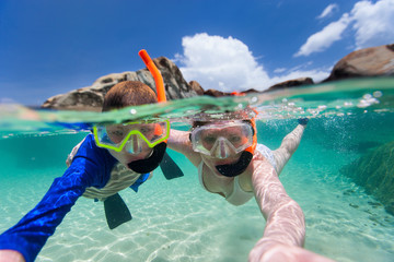 Family snorkeling in tropical water Wall mural