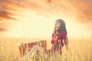 Beautiful brunette women with suitcase on autumn meadow in sunse