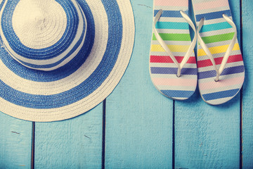 beach slippers and hat on blue wood