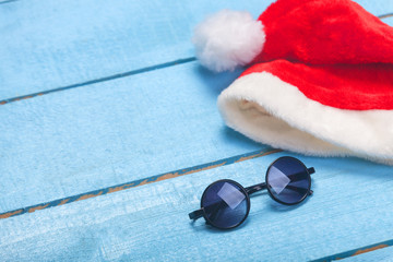 Sunglasses and christmas hat on blue wood