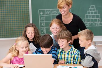 lachende schulkinder schauen auf laptop