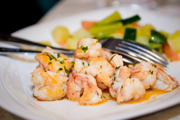 Fried shrimps in sauce with herbs and steamed vegetables
