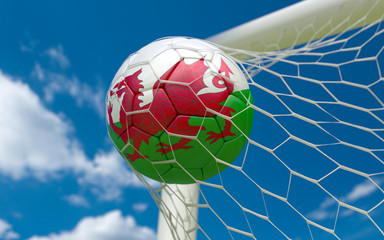 Wales flag and soccer ball in goal net