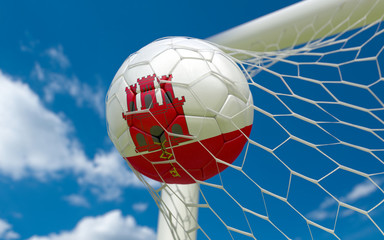 Gibraltar flag and soccer ball in goal net