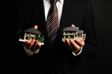 黒い背景で住宅の模型を持っているスーツの男性