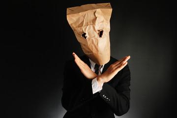 紙袋で覆面したスーツのビジネスマンが手でバツをしている