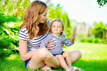 Young mother with little daughter in park