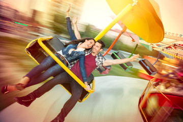 Poster Attraction parc Young happy couple having fun at amusement park