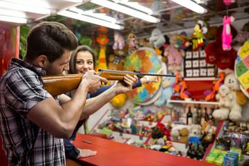 Young fun couple playing shooting games