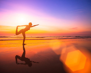 Silhouette of a woman practicing yoga on the beach at sunset.
