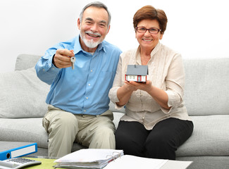 Happy senior couple holding a small house