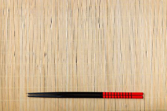 Two chopsticks on sushi mat background