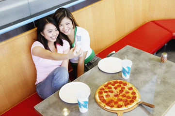 Two teenage girls taking picture with cell phone at pizza restaurant