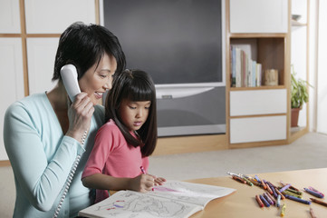 Mother talking on the phone as her daughter draws