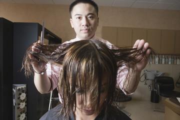Asian male hairstylist cutting hair