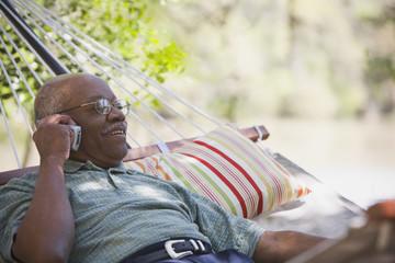 Senior African man using cell phone in hammock