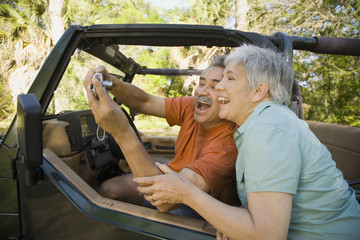 Senior Hispanic couple taking self-portrait with jeep