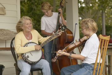 Mother and sons playing instruments together on porch