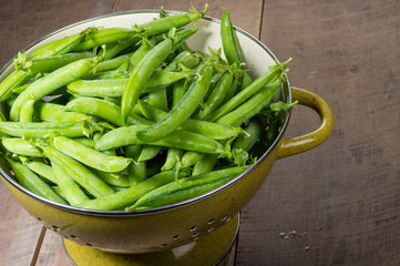 Fresh green pea pods in a bowl