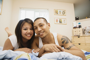 Portrait of Asian couple on bed