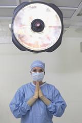 Female surgeon praying in operating room