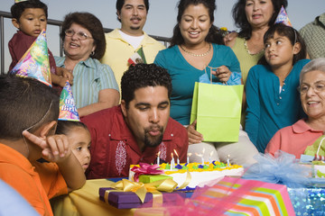 Hispanic man blowing out candles on birthday cake with family