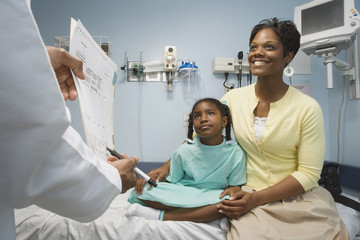 African girl in hospital bed with mother talking to doctor