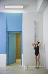 Asian woman in bathing suit taking shower