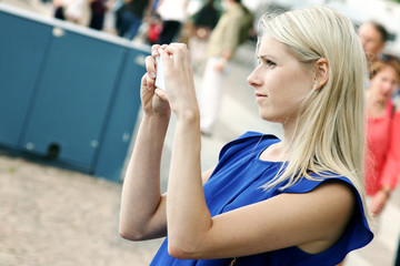 woman taking picture with mobile phone on the street
