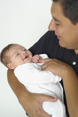 """Hispanic father smiling at baby,"""