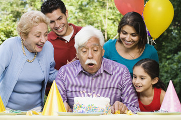 Senior Hispanic man blowing out birthday candles with family in park