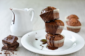 Cupcakes with liquid chocolate on a white plate