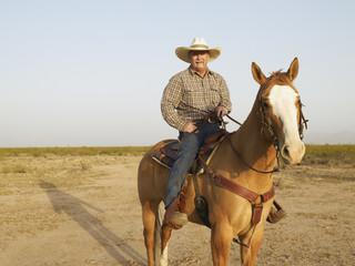 Mixed Race man riding horse