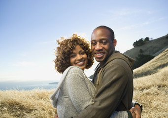 African American couple hugging in field