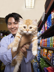 Asian man holding cat in pet store