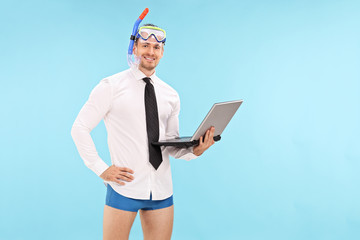 Businessman with a diving mask holding a laptop