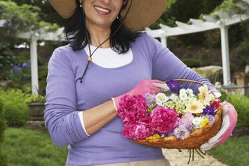 Hispanic woman holding basket of flowers