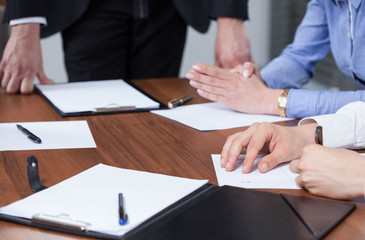 Hands and clipboards during business meeting