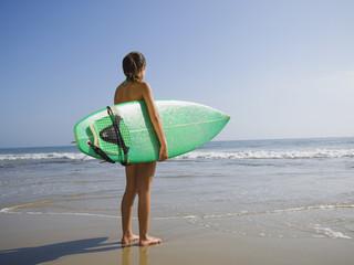 Hispanic girl holding surfboard