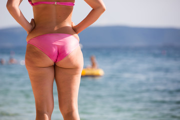 Woman in pink bikini at a beach, watching the sea