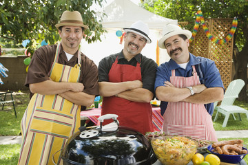 Hispanic men with arms crossed at barbecue
