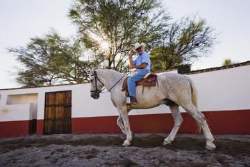 Hispanic man riding horse
