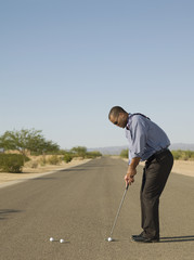 African businessman playing golf in road