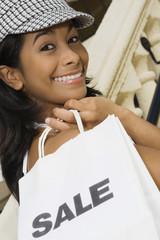 Hispanic woman holding shopping bag