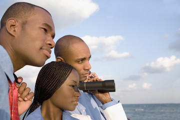 African businesspeople looking through binoculars