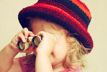close up of cute kid looking through binoculars. toned image