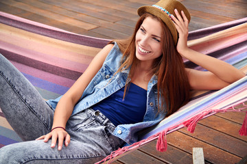 beautiful young woman resting in a hammock